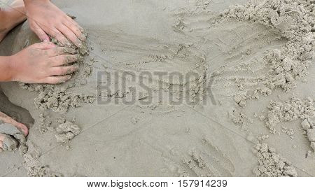 Caucasian kid plays with sand and builds sandcastle on beach