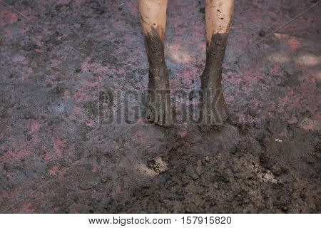 Dirty barefeet kid walking on muddy ground
