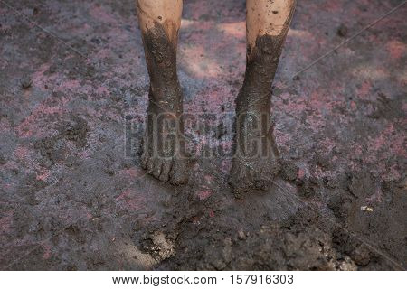 Closeup view of dirty barefeet kid walking on muddy ground