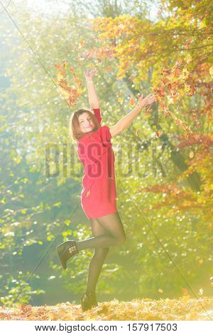 Young woman tossing leaves. Girl playing in autumnal park. Nature outdoor relax scenery concept.