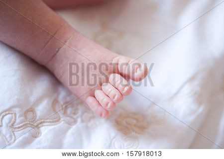 Details of caucasian little baby foot on bed