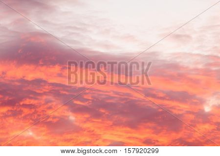 Romantic and dramatic cloud formation on dusk sky. Red and black warm landscape with sunlight.