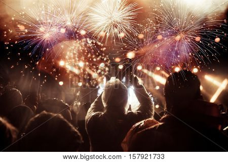 cheering crowd watching fireworks at New Year - holiday celebration background
