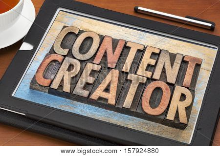content creator - word abstract in vintage letterpress wood type printing blocks on a digital tablet