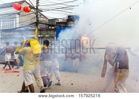 PHUKET TOWN, THAILAND, OCTOBER 09, 2016 : Taoist devotees are carrying palanquin containing an idol, under heavy firecrackers explosions during vegetarian festival in Phuket town, Thailand