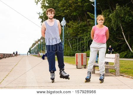 Hobby and spending free time in summer. Sport and exercising. Healthy body and wellbeing. Couple have fun together rollerskating outdoors.