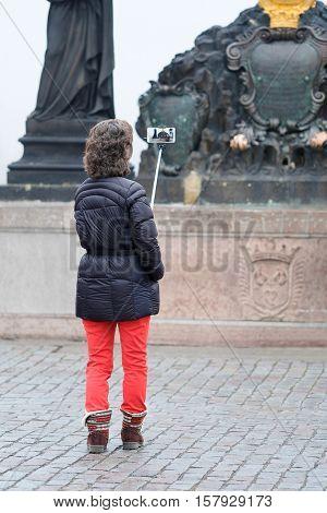 Tourist makes photo on Charles Bridge in Prague, Czechia