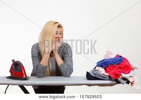 Housewife problems concept. Shocked woman standing behind ironing board having lot of clothes to iron. Studio shot on white background
