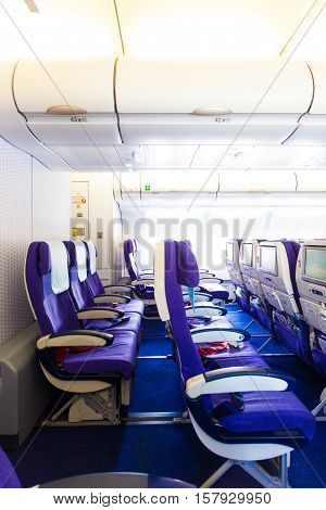 Empty non reclining last rows of economy class on airplane with purple seats