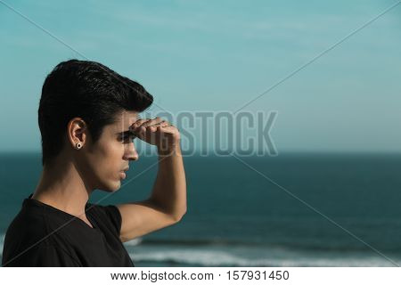 Portrait of young handsome brazilian guy with black hair and earring standing in front of ocean and looking ahead shielding his eyes from bright sun summer day clear sky Rio de Janeiro