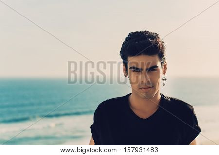 Complacent handsome brazilian guy with brown eyes black t-shirt and cross-earring on summer day teal blurred ocean and horizon in background Rio de Janeiro Brazil