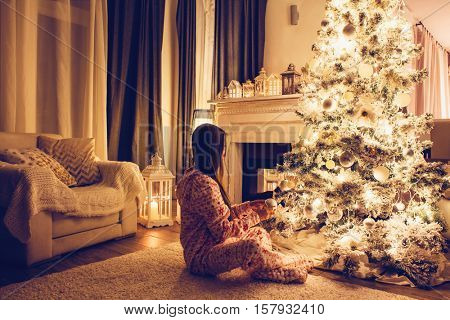 Child in pajama decorating the Christmas tree in illuminated room some december night, winter weekends, cozy scene
