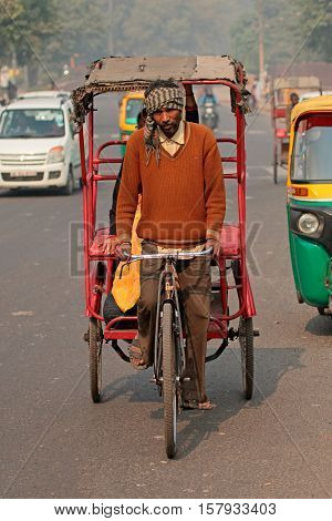 DELHI, INDIA - NOVEMBER 20, 2015: Cycle rickshaw rider transports a passenger in the crowded traffic with visible smog of air pollution