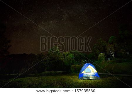 Illuminated Yellow camping tent under stars at night