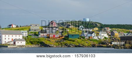 Bona Vista hillside and shoreline.  Bright colored homes nestled in hillside, coastal villages along the fingers of the Island of Newfoundland, Canada.