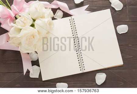 White Roses Flower With Ribbon Are On The Notebook