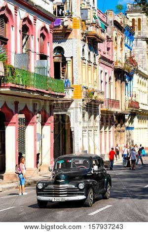 HAVANA,CUBA- NOVEMBER 20,2016 : Street scene with colorful old buildings and a classic american car in Old Havana