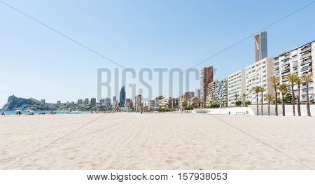 Apartment building form long view backdrop to Benidorm beach Spain unrecognisable people at seaside.