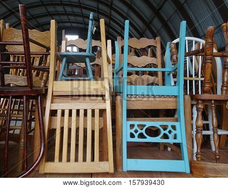 Two antique wooden blue chairs, one adult and one child size, stand out in an array of neatly stacked seats waiting for the next celebration in a rustic setting.