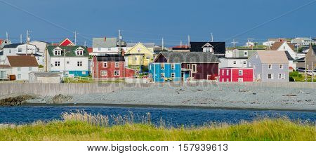 Small town with bright colored homes all over the coastal villages along the fingers of the Island of Newfoundland, Canada.