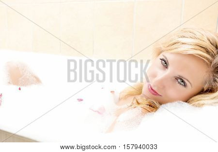 Passionate Sexy Blond Female Relaxing in Foamy Bath Covered with Flowery Petals. Horizontal Image Orientation