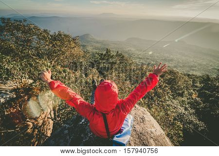 Happy man sitting on a cliff side with arms raised up