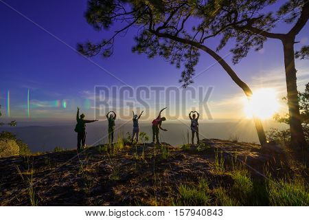 group of people, Happy hiking standing on a cliff side with arms raised up