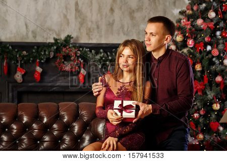 Loving couple and Christmas. He hugs his girlfriend and gives her a Christmas present.
