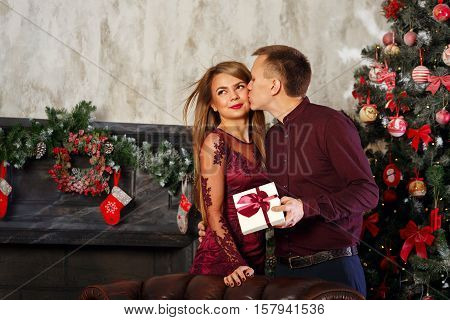 Loving couple and Christmas. Man kissing his girlfriend in gratitude for the best Christmas gift. In the background a beautiful Christmas tree.