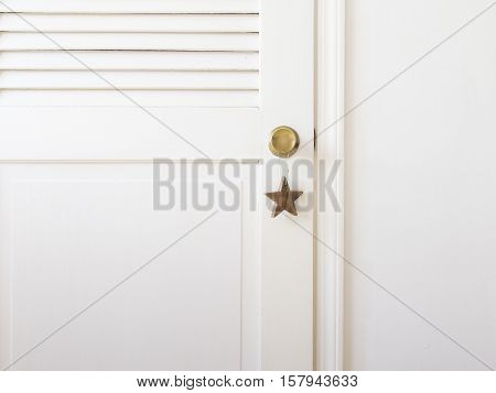 wooden Christmas toy in the interior. wooden star hanging on the doorknob. Christmas decorations. the concept of minimalism