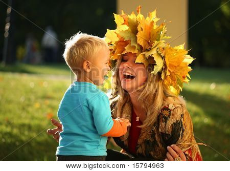 Young beautiful mother playing with her little sun in an autumn park.