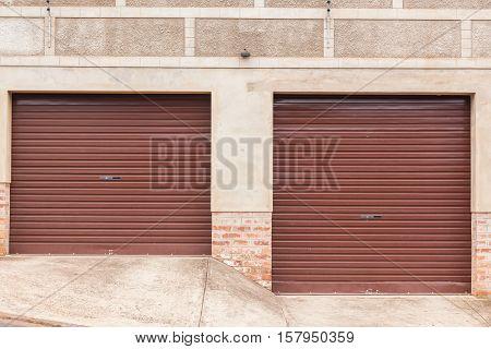 Two metal roll up garage doors outside roadside.
