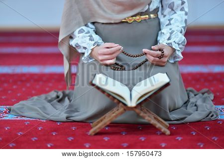 Young muslim woman praying alone in mosque