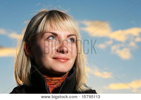 Beautiful blond girl over blue sky at sunset