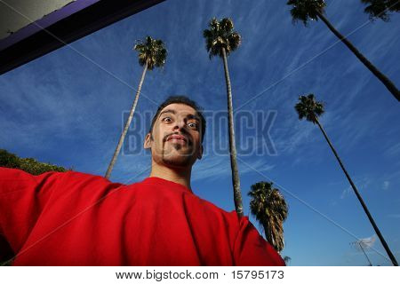 Portrait of a young man in California, blue sky and palm trees behind him.