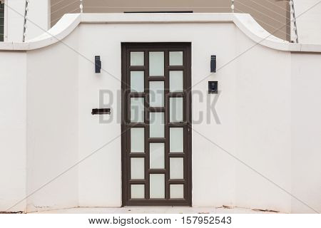Roadside door entrance decor electrified security wires on boundary walls.