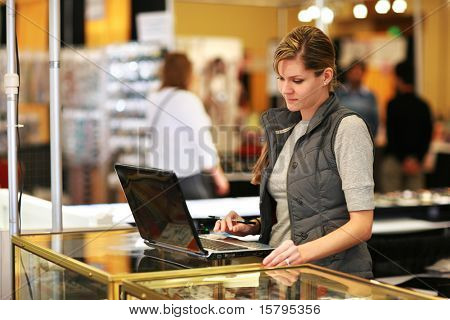 Young businesswoman using laptop computer at trade show.