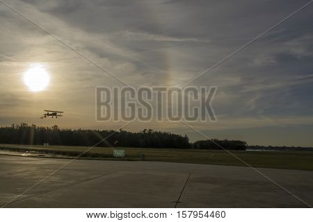 Silhouette of biplane about to land during sunset