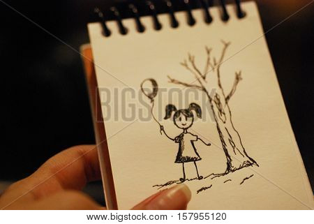 Sketch of a girl holding balloons near a tree. Done in a notebook with a pen.