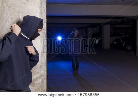 Criminal with knife waiting for a woman. Robbery concept