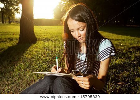Beautiful young woman writing outdoors in a park at sunset
