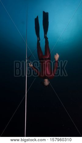 Free diver descending along the rope in the depth. Constant weight discipline