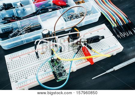 Set of electronic details for robotics construction. Breadboard with special connections, colorful wires and tool box on table ready for use. Hobby, electronics development