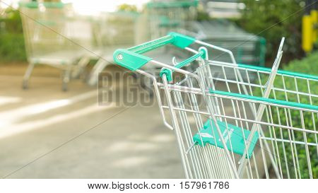 Shopping and mall concept - Close up shopping cart on car parking in mall with copyspace