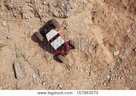 Rc suv riding offroad rally, top view, free space. Toy crawler driving on trace, fenced with blue string. Entertainment, competition, activity, explorer concept. The off-road track background.