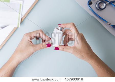 Top view of female doctor holding an aerosol inhaler near a laptop and stethoscope on her desk - Medical respiratory disease