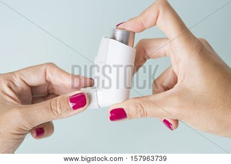 Close up of female hands holding an aerosol inhaler - Medical respiratory disease