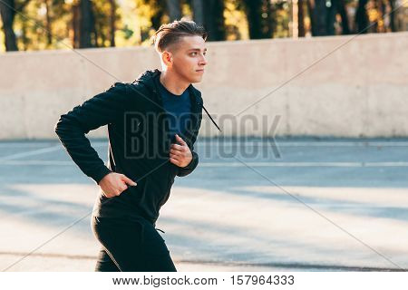 Handsome man jogging alone training for marathon. Profile photo of young male sprinter on open-air stadium, free space for text. Sport, workout, fitness concept
