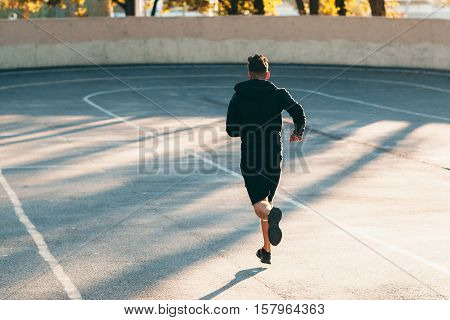 Runner on track at sport stadium, free space. Back of professional sportsman, training on open-air sports field. Fitness, workout, healthy lifestyle concept