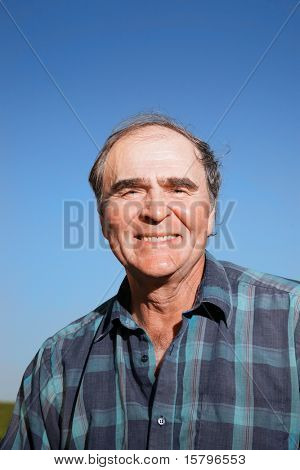Portrait of a happy senior man outdoors over blue sky.